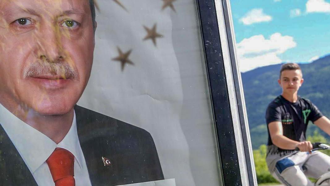 Photo: Cyclist glances at Portrait of Erdoğan.